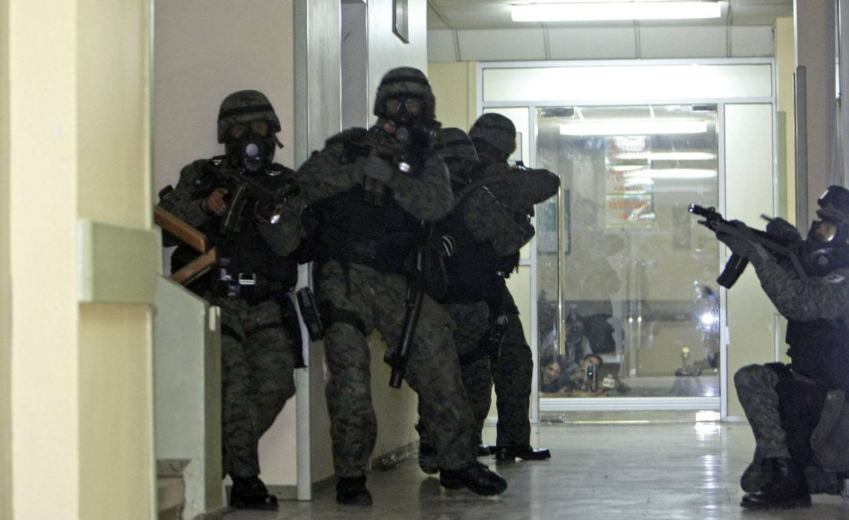 Soldiers enter the police hospital where Ecuador's President Rafael Correa was holed up, in Quito. Dolores Ochoa/AP