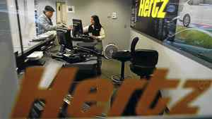 A customer is checked out by a sales associate as seen through the window of a Hertz car rental location April 26, 2010 in New York City.
