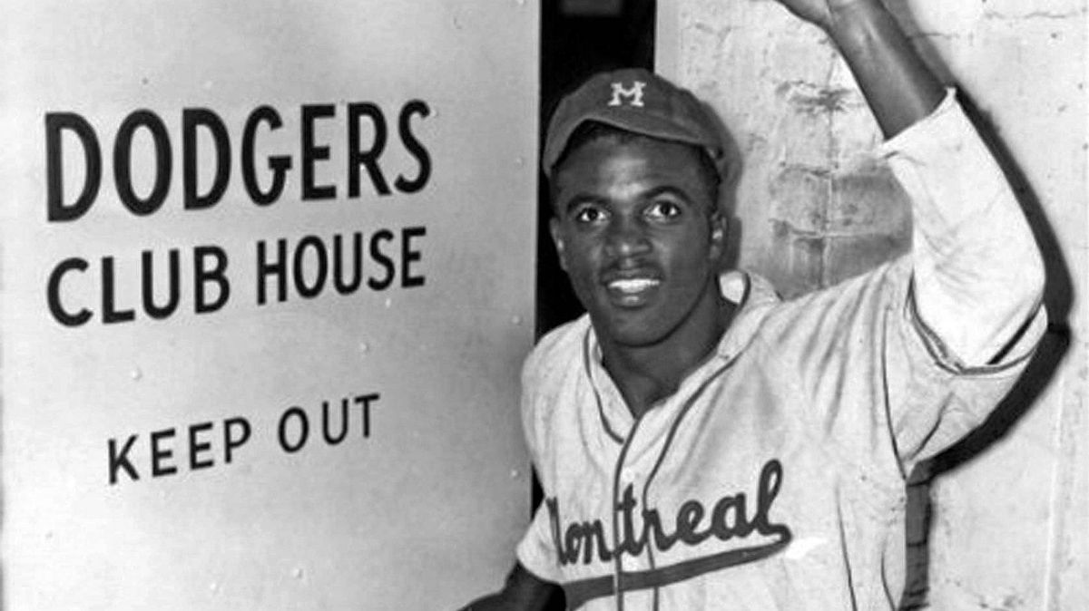 Jackie Robinson, in 1947, wearing his Montreal Royals uniform, steps into the Brooklyn Dodgers clubhouse for the first time.