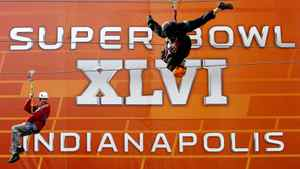 Fans ride on a zip line in downtown Indianapolis, Indiana, February 3, 2012, ahead of the NFL's Super Bowl XLVI football game. Super Bowl XLVI between the New England Patriots and the New York Giants is set for play on February 5. REUTERS/Mike Segar