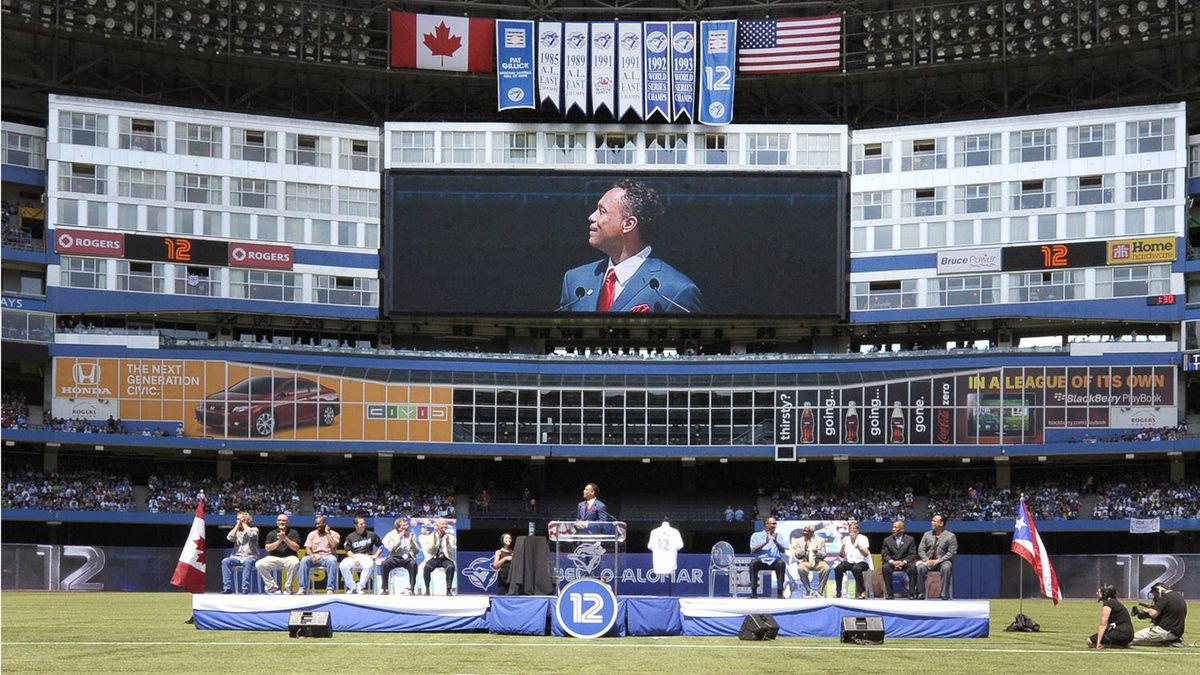 Former Toronto Blue Jays second baseman Roberto Alomar watches a banner unfurl during a ceremony to retire his number 12 jersey. REUTERS/Mike Cassese