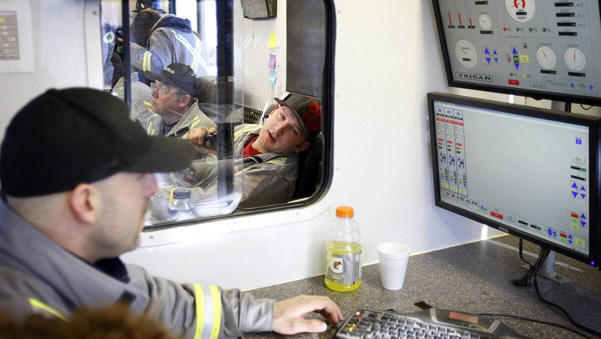 Trican Well Service employees monitor the hydraulic fracturing process from an onsite control centre near Bowden, Alta., Tuesday, Feb. 14, 2012.