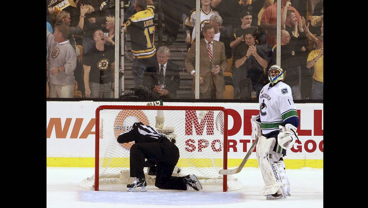 Boston Bruins fans react as Vancouver Canucks Roberto Luongo looks on as a linesman retrieves the puck from the net after the fourth goal during the first period of the NHL Stanley Cup Final Game 6 in Boston on June 13, 2011. (Photo by Peter Power/The Globe and Mail)