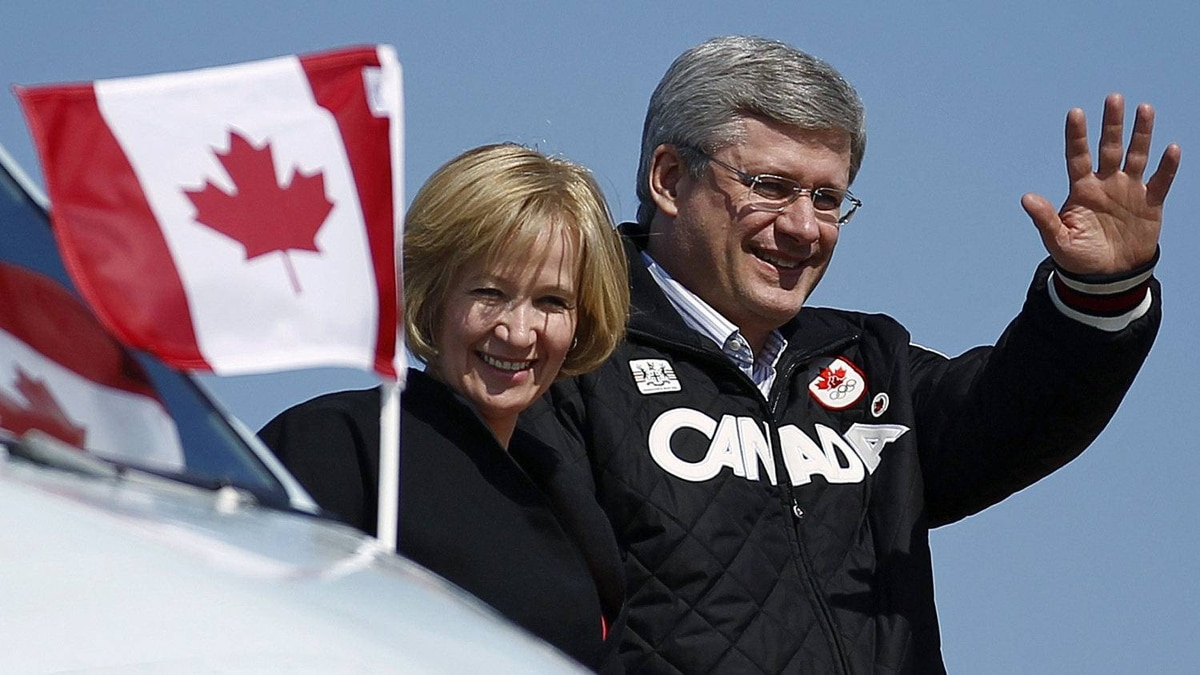 Conservative Leader Stephen Harper waves as he disembarks his campaign plane with his wife, Laureen, in Comox, B.C. on April 23, 2011.
