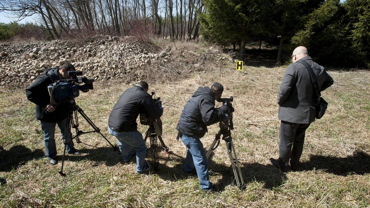 Members of the media film at the site where Tori Stafford's body was found near Mount Forest, Ont..