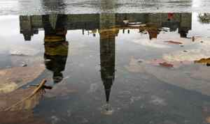 The Peace Tower is reflected in a puddle.