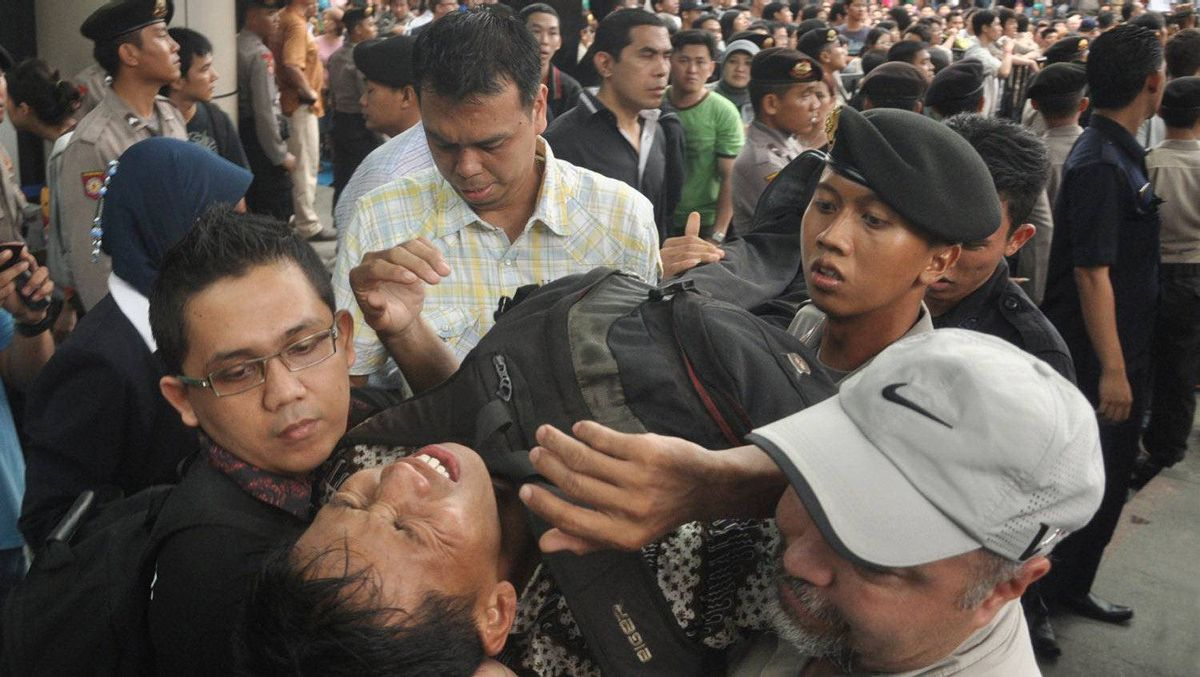 This file photo taken on November 25, 2011 shows security personnel evacuating a man after he collapsed while queueing for discounted BlackBerry smartphones at a mall in Jakarta.