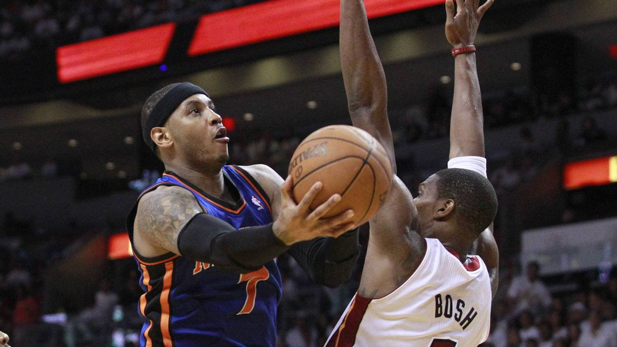 New York Knicks forward Carmelo Anthony (L) drives to the basket past Miami Heat forward Chris Bosh in the second half during Game 1 of their first round NBA Eastern Conference basketball playoff in Miami, Florida April 28, 2012. Miami won 100-67.REUTERS/Andrew Innerarity