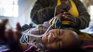 A mother tries to calm her young son who is suffering from malaria at a hospital in Lubumbashi.