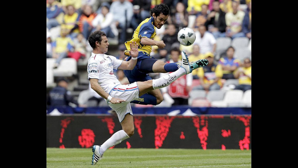 America striker Daniel Marquez, right, battles for the ball with Queretaro's defender Adrian Romero during their Mexican league championship soccer match at the Azteca stadium in Mexico City Feb. 6, 2011.