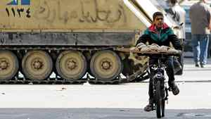An Egyptian boy rides his bicycle near an army tank as he sells bread in central Cairo on January 31, 2011