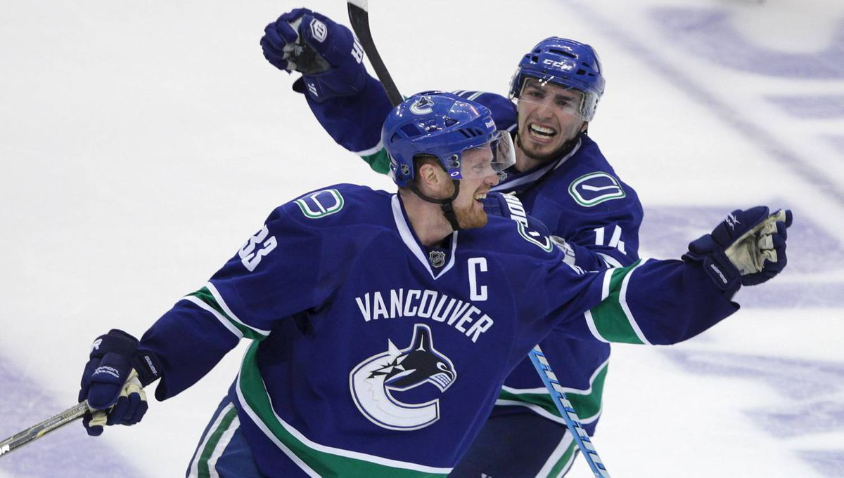 Vancouver Canucks Alex Burrows and Vancouver Canucks Henrik Sedin celebrate their win the 5th period against San Jose Sharks of game five of the NHL Western Conference final in Stanley Cup playoff hockey action in Vancouver May 24, 2011. (John Lehmann/The Globe and Mail)