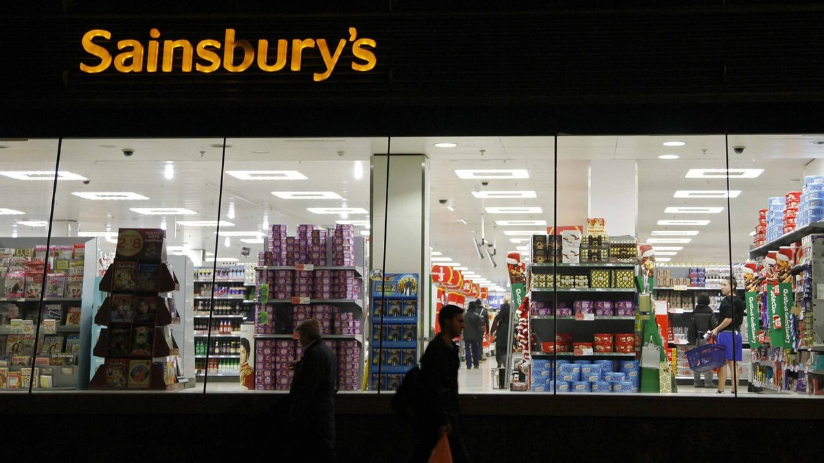 People walk past a Sainsbury's store in south London