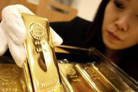 An employee of Tanaka Kikinzoku Jewerly K.K. displays a gold bar at the company's store in Tokyo in this January 29, 2008 file photo.