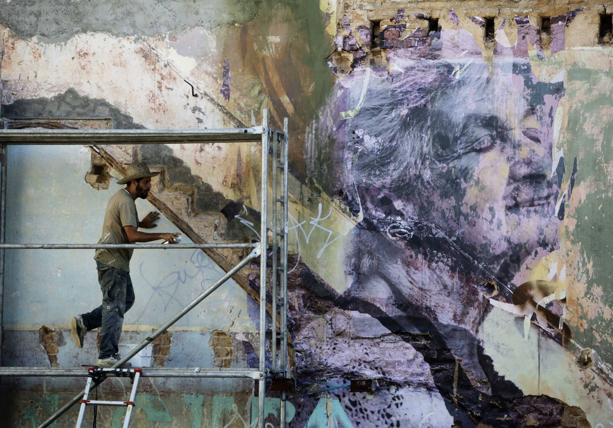 Cuban-American artist Jose Parla works on a creation on a building wall in Havana, for the upcoming 11th Havana Biennial contemporary art exhibition.