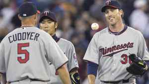 Minnesota Twins closing pitcher Joe Nathan, right, has the ball tossed to him while celebrating with teammates Michael Cuddyer, left, and Tsuyoshi Nishioka following the Twins' 4-3 win over the Toronto Blue Jays during MLB baseball action in Toronto Sunday, April 3, 2011. THE CANADIAN PRESS/Darren Calabrese