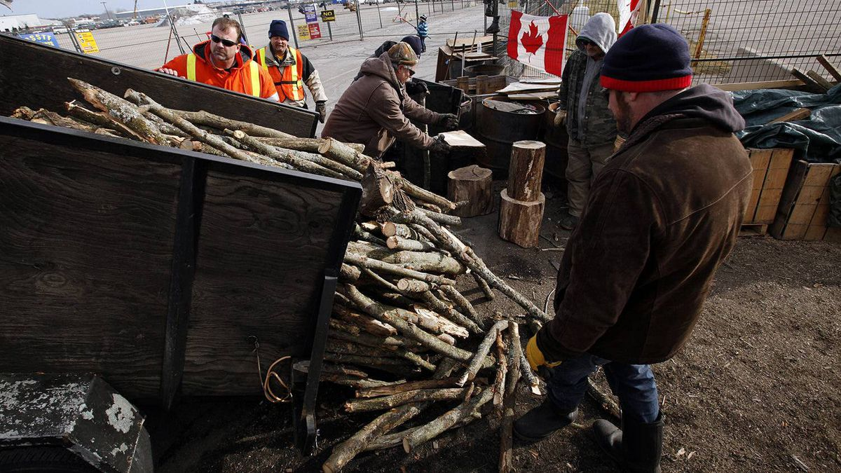 Electro-Motive Canada employees move wood that was dropped off on the picket line outside the subsidiary of Caterpillar in London on Feb. 8, 2012.