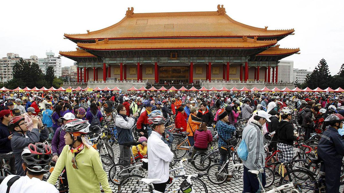 People gather with their bicycles at the Chiang Kai-shek Memorial Hall in Taipei December 31, 2011. Hundreds of thousands people participated in a bike ride around Taiwan on New Year's Eve as part of an attempt to achieve a Guinness World Record of the largest bicycle parade in the world. Various groups began from 1000 starting points around the island and cycled clock-wise towards the next starting point within one hour.