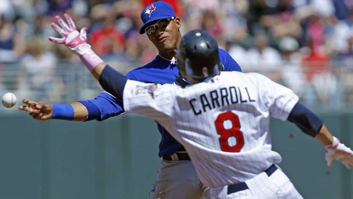 Toronto Blue Jays' shortstop Yunel Escobar throws around Minnesota Twins' Jamey Carroll (8) to complete a double play at first base during the third inning of their American League MLB baseball game at Target Field.