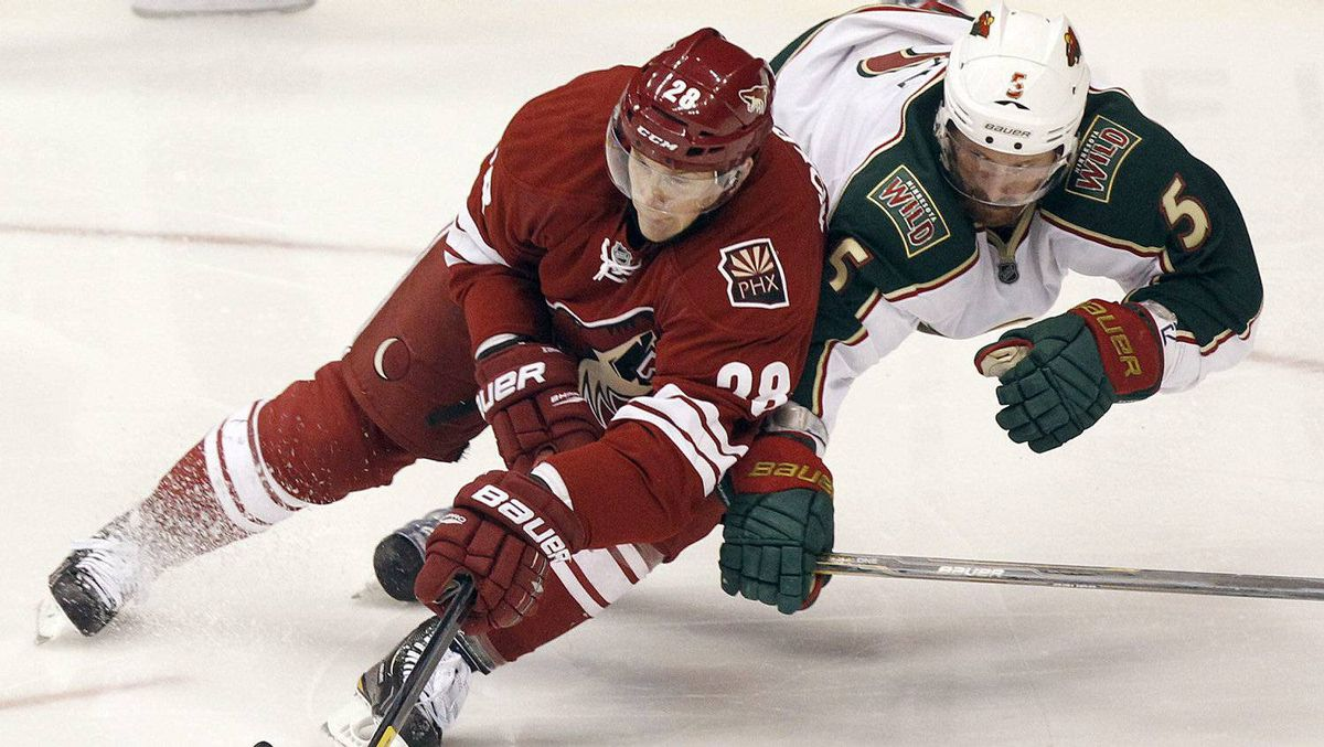 Phoenix Coyotes left winger Lauri Korpikoski, left, of Finland, reaches to gain control of the puck as he is checked by Minnesota Wild defenseman Greg Zanon, right, in the third period of an NHL hockey game Saturday, Dec. 10, 2011 in Glendale, Ariz. The Wild won 4-1. (AP Photo/Paul Connors)