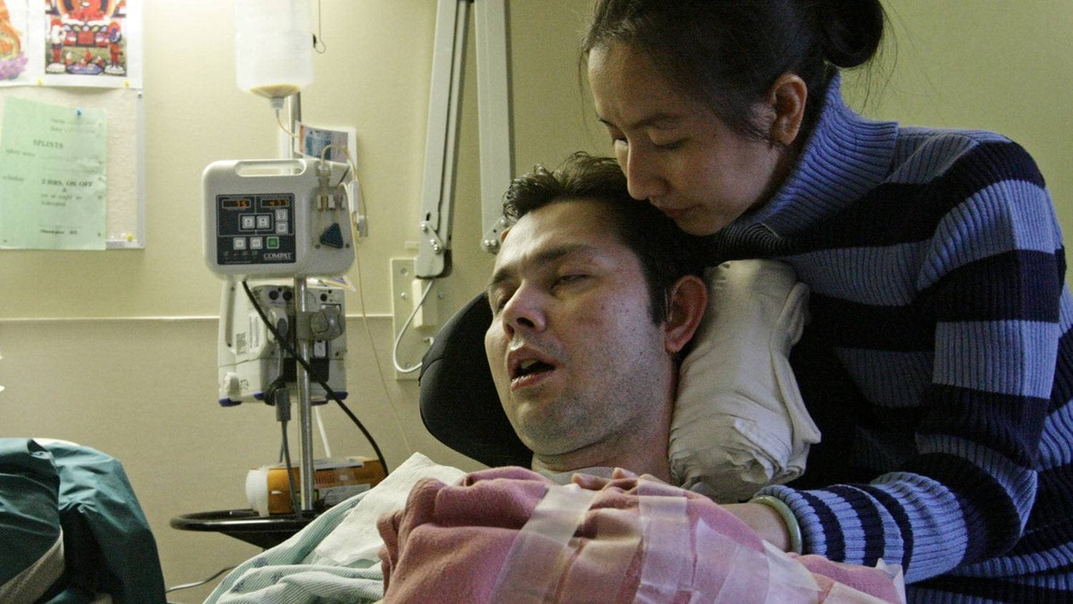 Michael Phan is comforted by his wife, Le Phuong, at Royal Columbian Hospital in New Westminster, B.C., on Thursday October 16, 2008.