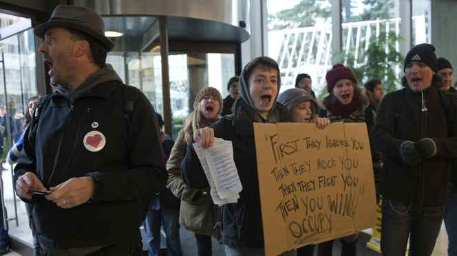 A group of protestors from the nearby Occupy Vancouver encampment demonstrate in the lobby of a downtown office tower Thursday, Nov. 17, 2011.