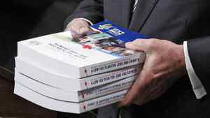 Canada's Finance Minister Jim Flaherty holds copies of his budget in the House of Commons in Ottawa on March 22, 2011.