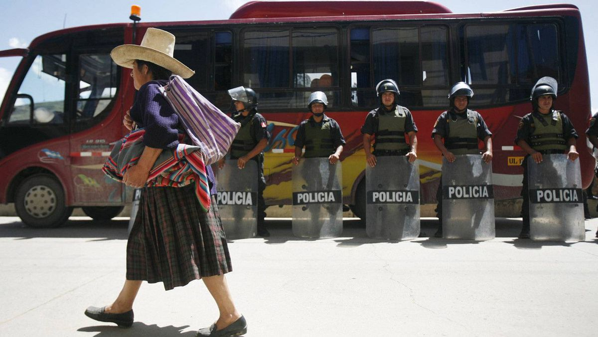 An Andean woman walks next to police officers during the second day of strike against Newmont's proposed $4.8 billion Conga gold mine at the Peruvian city of Cajamarca.