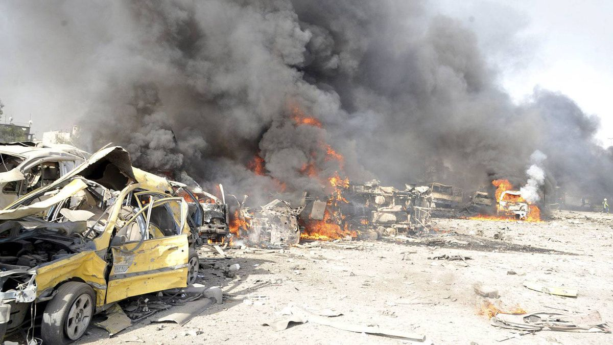 Smoke rises from the wreckage of mangled vehicles at the site of an explosion in Damascus on May 10, 2012.