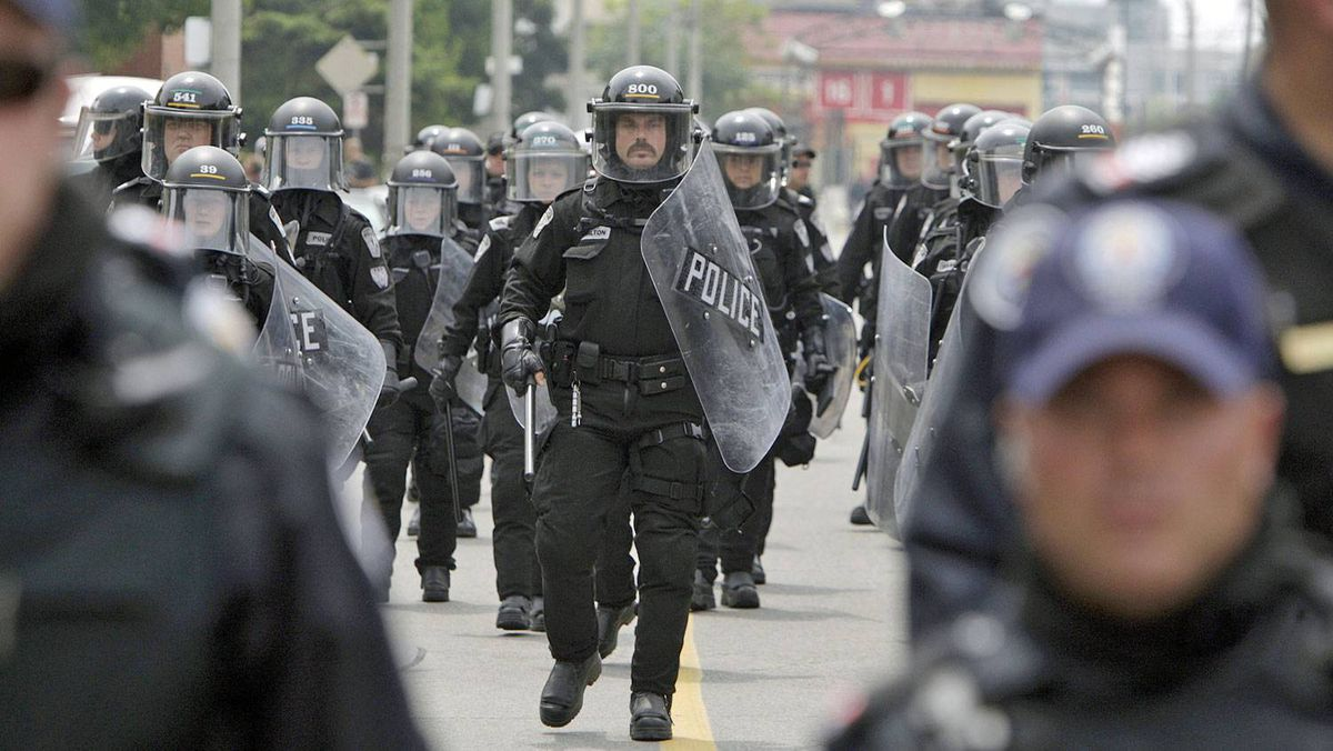 Police in riot gear walk north on Pape Avenue while clashing with citizens near the temporary G20 detention center on Eastern Avenue in Toronto, June 27, 2010.
