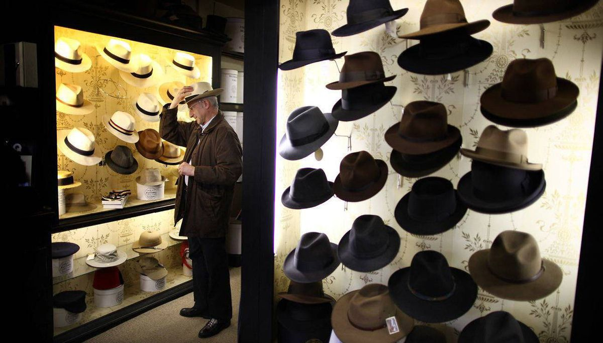 A customer tries on a Panama hat.