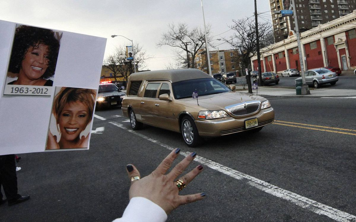 A fan holds up pictures of late singer Whitney Houston as a hearse carrying her casket drives from New Hope Baptist Church to Whigham Funeral Home in Newark, New Jersey February 18, 2012.