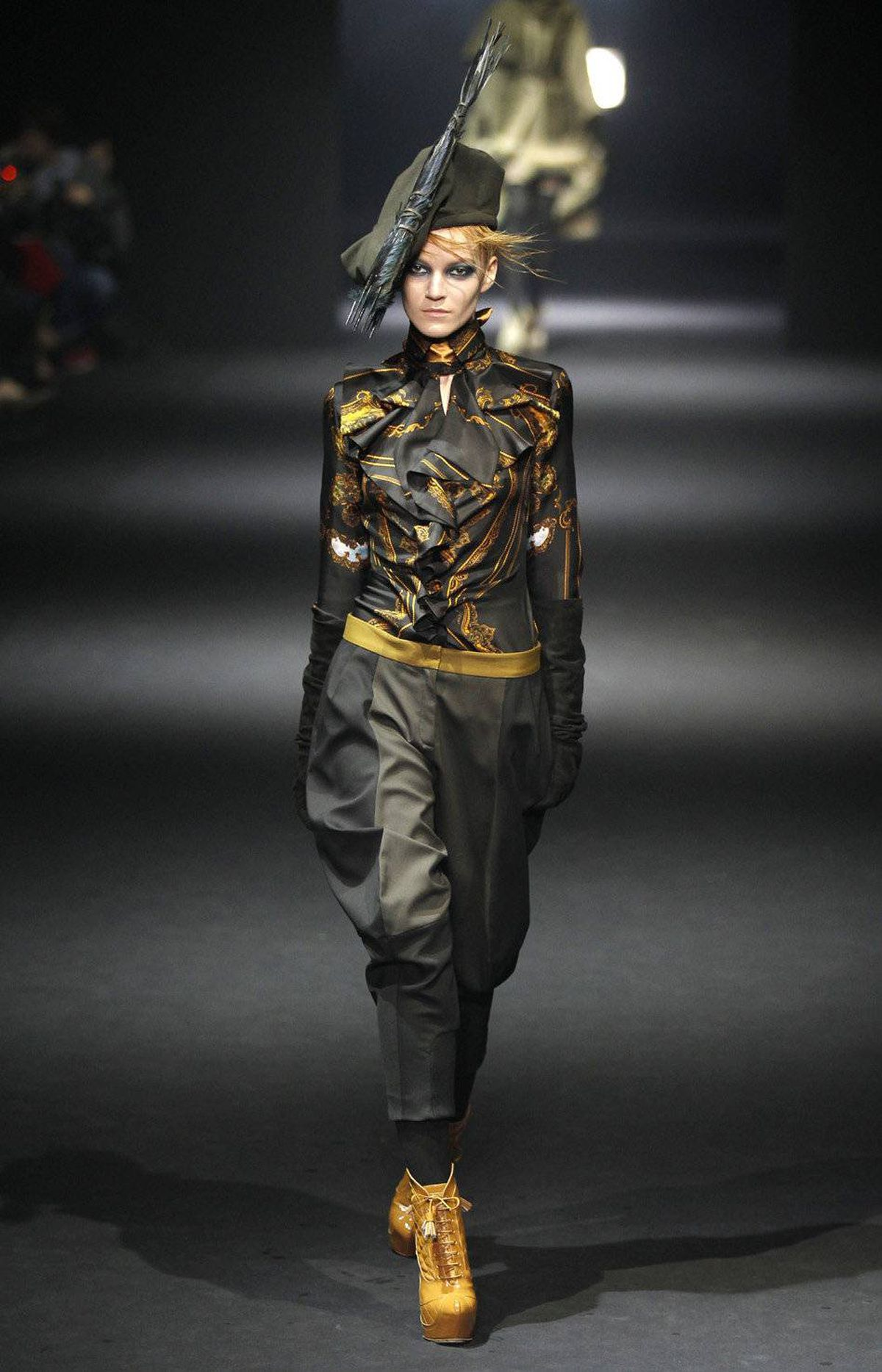 Fuller, jockey-style trousers also appeared at John Galliano, which is under the creative helm of Bill Gaytten, who is currently also designing for Christian Dior. Inspired by the illustrator Aubrey Beardsley, he played with ruff collar blouses, equestrian elements and caps fronted with clusters of branches.