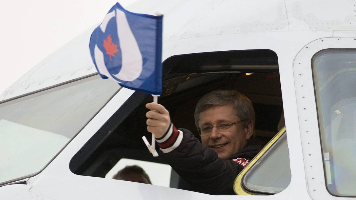 Prime Minister Stephen Harper waves a Conservative party flag from the cockpit of his campaign plane as he arrives in Ottawa,Tuesday May 3, 2011.