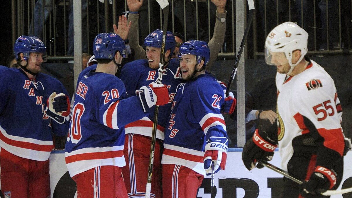The New York Rangers celebrate a goal by Marc Staal, hidden, as Ottawa Senators' Sergei Gonchar skates past during the first period in Game 7 of their NHL Eastern Conference quarter-final playoff hockey game in New York, April 26, 2012.