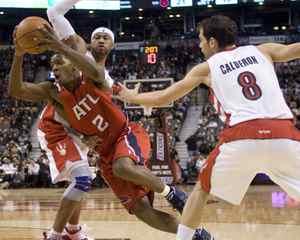 Atlanta Hawks' Joe Johnson, left, drives between Toronto Raptors' Antoine Wright and Jose Calderon, right, during half NBA action in Toronto on Friday Dec. 11, 2009. THE CANADIAN PRESS/Chris Young