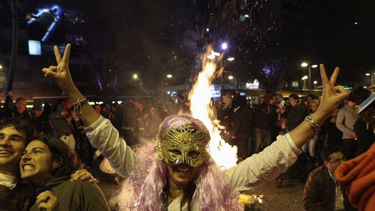 Tourists pose beside burning puppets during year-end celebrations at the Plaza Foch in Quito, Ecuador, January 1, 2012.