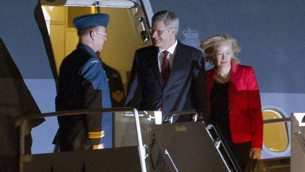 Canada's Prime Minister Stephen Harper (C) arrives with wife Laureen Teskey (R) at the airport in Honolulu, Hawaii, on November 11, 2011 for the Asia-Pacific Economic Cooperation (APEC) Summit. The United States is hosting this year's APEC forum for the first time since 1993, with leaders from the 21 member economies convening on the island of Oahu on November 12-13.