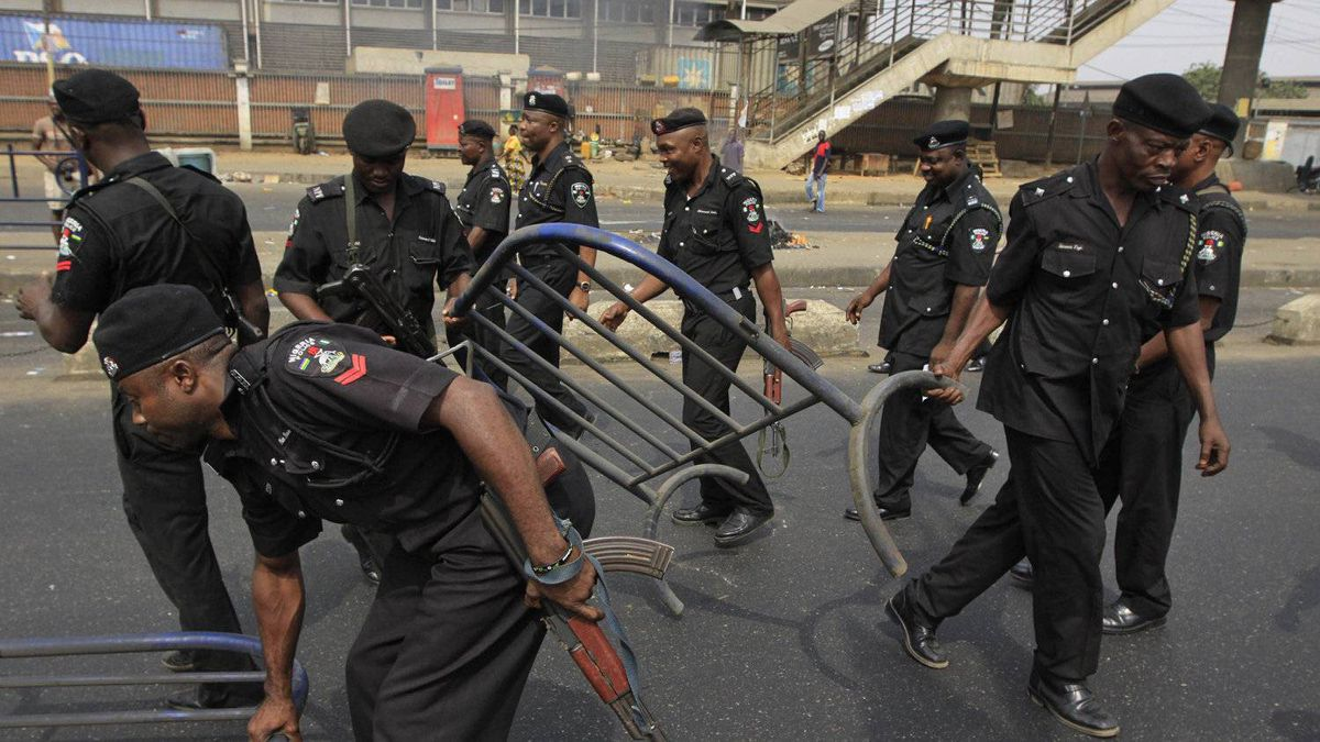 Policemen remove barricades mounted by protesters following the removal of a fuel subsidy by the government in Lagos Nigeria, Monday, Jan. 9, 2012. A national strike paralyzed much of Nigeria on Monday, with more than 10,000 demonstrators swarming its commercial capital to protest soaring fuel prices and decades of government corruption in the oil-rich country.