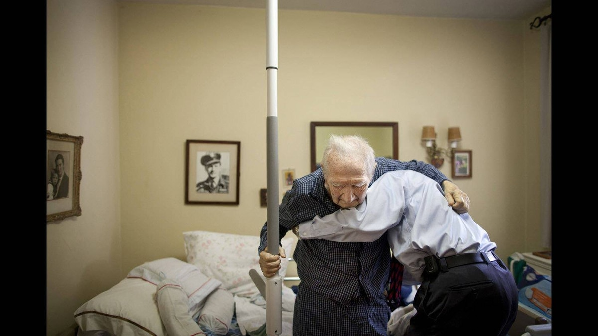 NPAC Pictures of The Year, 1st Place Social Issues - Dr. Samir Sinha helps 92-yr-old patient Steven out of bed during a house call visit April 5, 2011. Dr. Sinha is one of just a few doctors who work with the SPRINT program to provide house visits to elderly patients.