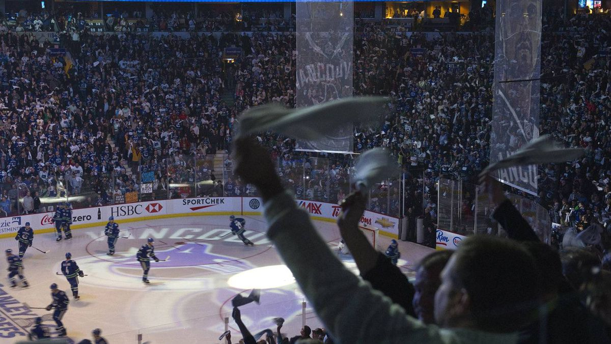 Vancouver Canucks fans wave white towels as the team comes on the ice. REUTERS/Andy Clark