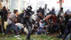Riot police chase opposition UDPS supporters caught in a cloud of tear gas outside N'Djili airport in Democratic Republic of Congo's capital Kinshasa November 26, 2011.