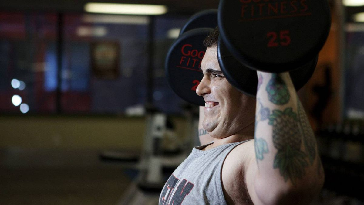 Vegan chef Doug McNish, who is adorned in tattoos symbolizing his plant-based diet, strains as he works out with free weights in Toronto on Thursday, March 15, 2012.