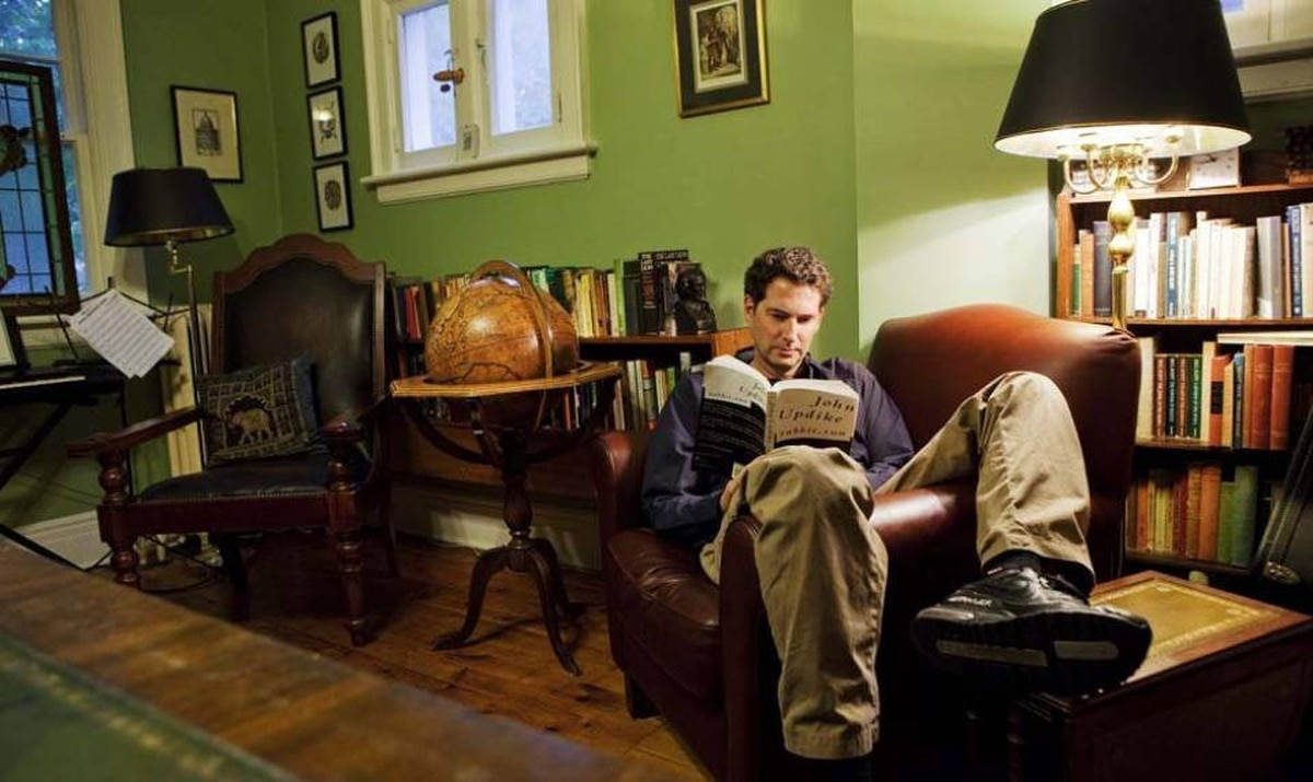 Kenneth Oppel reads in the library of his Toronto home.