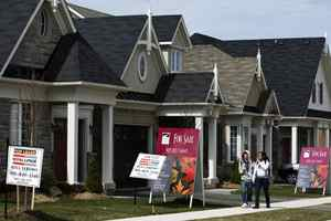 People walk past new homes that are for sale in Oakville, Ont.