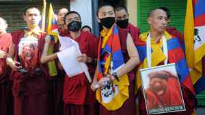 Tibetan monks hold placards showing the monks who had set themselves on fire to protest Chinese rule in Tibet during a march in Dharamshala on Oct. 14, 2011.