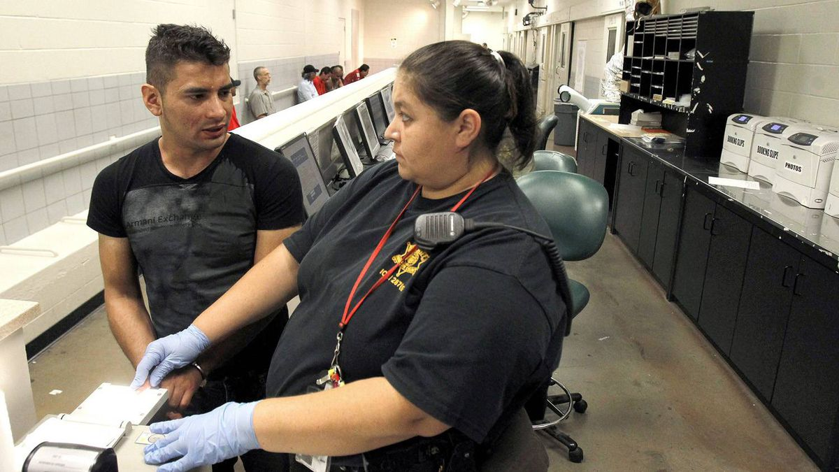 A suspect, left, is fingerprinted by a Maricopa Country Sheriff's detention officer on Monday, July 26, 2010 to check his immigration status at a 287(g) processing station after being brought from the Maricopa County Sheriff's Office Fourth Avenue Jail in Phoenix.