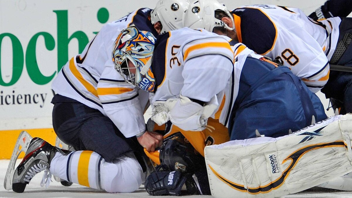 Goalie Ryan Miller #30 of the Buffalo Sabres punches Jordin Tootoo #22 of the Nashville Predators at the Bridgestone Arena on December 3, 2011 in Nashville, Tennessee. (Photo by Frederick Breedon/Getty Images)