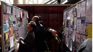 Job seekers look at the ads on display at a job fair in Toronto.