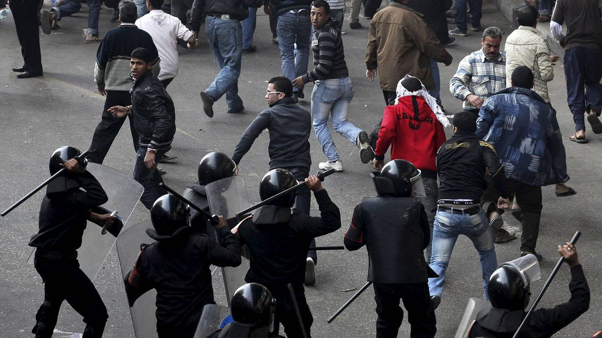 Egyptian protesters flee as riot police charge towards them in Cairo, Egypt, Friday, Jan. 28, 2011.